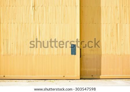 Close up of a yellow hangar door with black handle. Copyspace on door. - stock photo