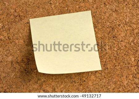 Close up of a yellow post note on corkboard.