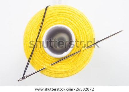 close up of a yellow sewing spool with a needle
