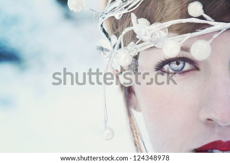 Close-up of a young attractive woman wearing an Icy headband and red lipstick. Focus is on the eye. - stock photo