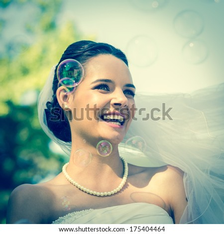 Close-up of a young beautiful bride looking at soap bubbles in the park - stock photo