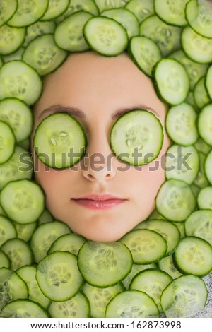 Close up of a young beautiful woman with facial mask of cucumber slices on her face at spa salon - stock photo