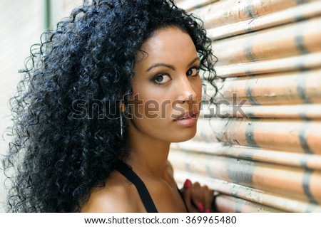 Close-up of a young black woman, afro hairstyle, with very curly hair in urban background