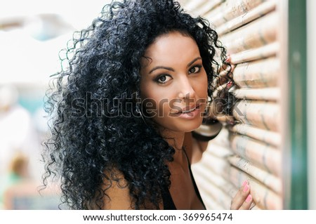 Close-up of a young black woman, afro hairstyle, with very curly hair smiling in urban background - stock photo