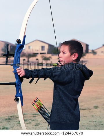 Close up of a young boy drawing back a bow and arrow