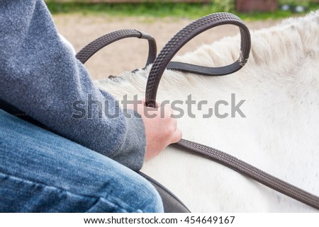 Close-up of a young boy holding the reins of a white pony in his hands