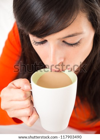 Close up of a young brunette woman sipping a cup of hot coffee - stock photo