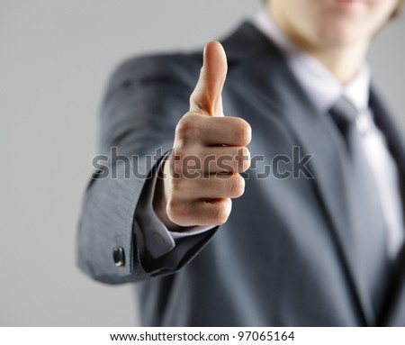 Close-up of a young businessman showing thumbs up. - stock photo