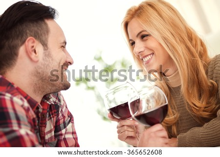 Close up of a young couple enjoying wine at home.They are sitting close to each other and drinking red wine. - stock photo