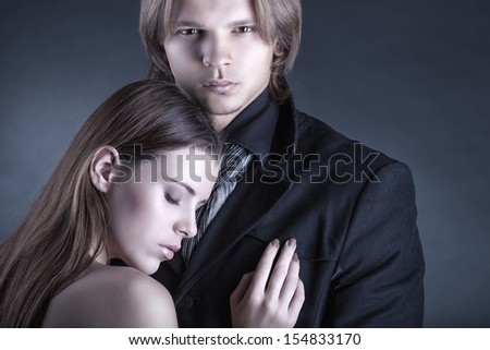 Close-up of a young couple on a dark background - stock photo