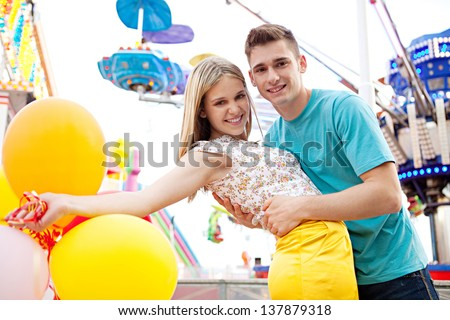 Close up of a young couple visiting fun fair park arcade being romantic during an early evening with lights and rides in the background. - stock photo