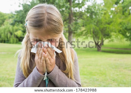 Close-up of a young girl blowing nose with tissue paper at the park - stock photo