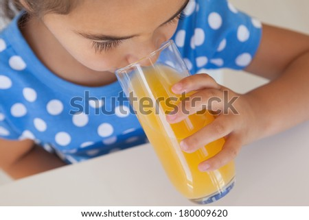 Close-up of a young girl drinking orange juice at home