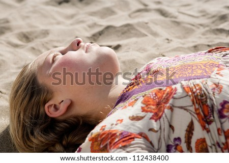Close up of a young girl laying down on a golden sand beach, relaxing. - stock photo