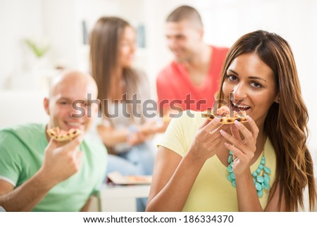 Close up of a young girl smiling and eating pizza with her friends in the background.