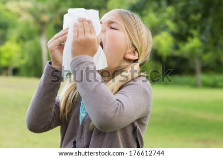 Close-up of a young girl sneezing into tissue paper at the park - stock photo
