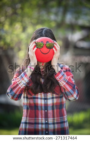 Close-up of a young girl with a balloon face with sunglasses on vertical - stock photo