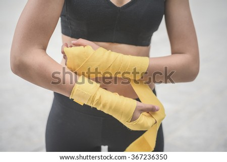 Close up of a young handsome caucasian brown hair woman wrapping her hands with a band, preparing herself for boxing training - sportive, healthy, fitness concept - stock photo