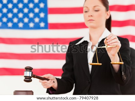 Close up of a young judge knocking a gavel and holding scales of justice with an American flag in the background - stock photo