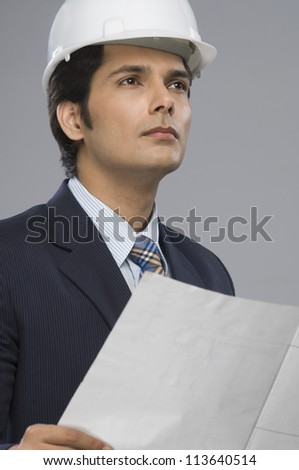 Close-up of a young male architect holding a paper