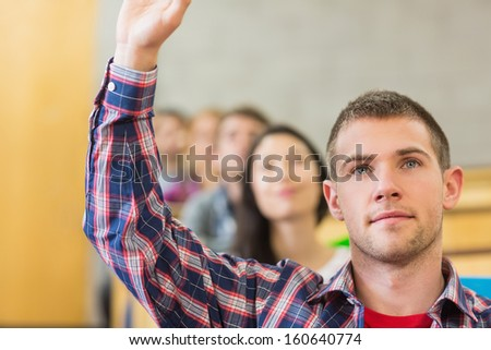 Close-up of a young male student raising hand by others in a row at the classroom - stock photo