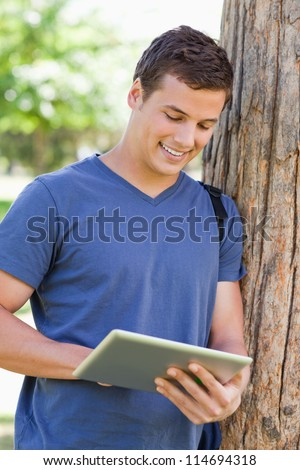 Close-up of a young man leaning against a tree while using a touch pad in a park - stock photo