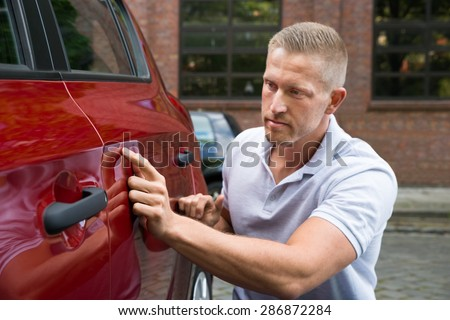 Close-up Of A Young Man Looking For Scratches On His Red Car