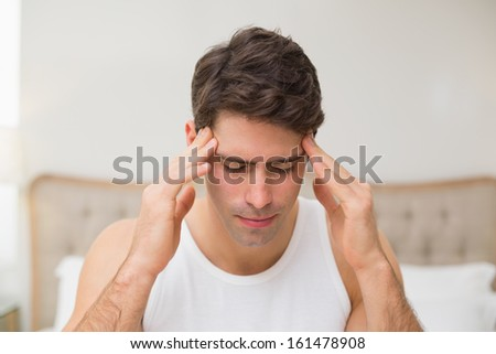 Close up of a young man suffering from headache in bed at home