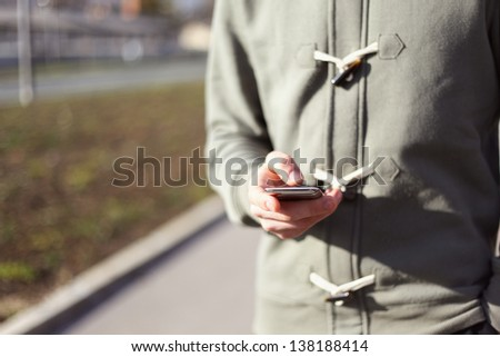 Close up of a young man typing text message on his smartphone - stock photo
