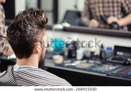 Close-up of a young man with his hair raised upwards sitting before the mirror at barbershop  - stock photo