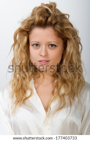 Close-up of a young smiling blonde girl just woke up from sleep, still in pajamas
