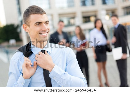 Close- up of a young smiling businessman while standing in front of office building separated from the rest of the business team. - stock photo