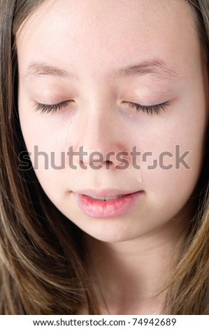 close-up of a young teen girl criying with eyes closed - stock photo