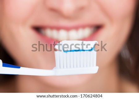 Close-up Of A Young Woman Brushing Her Teeth - stock photo