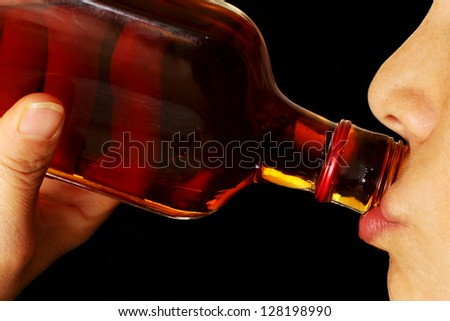 Close Up of a Young Woman Drinking Hard Liquor from the Bottle - stock photo