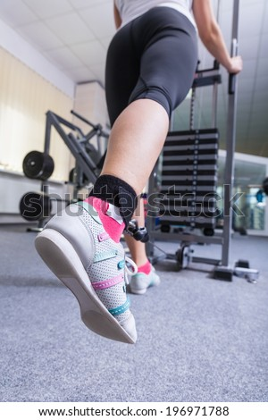 Close-up of a young woman foot in the gym working on the fitness equipment - stock photo