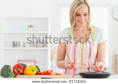 Close up of a young woman frying peppers in the kitchen