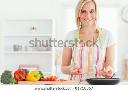 Close up of a young woman frying peppers looking into the camera in the kitchen