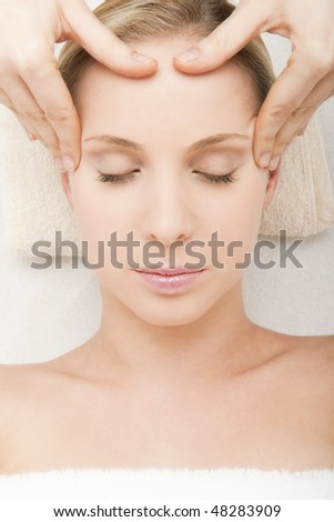 Close-up of a young woman getting spa treatment.