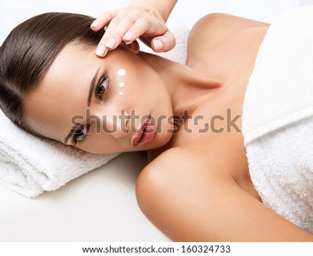 Close-up of a Young Woman Getting Spa Treatment. Cosmetic Cream on a Cheek. Skin Care