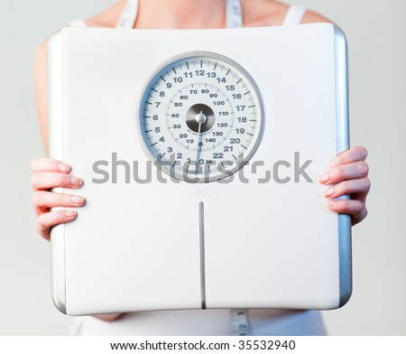 Close-up of a young woman holding a scales  with focus on scales - stock photo