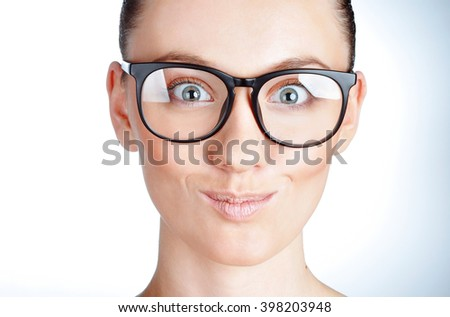 Close-up of a young woman in glasses looking funny and happy. Beauty studio shot isolated on white. Emotions, expressions - stock photo