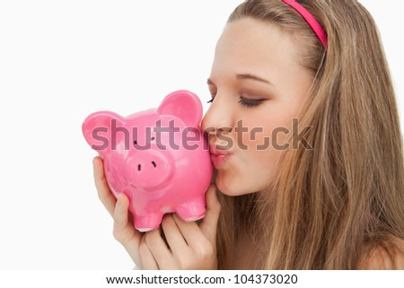 Close-up of a young woman kissing a piggy-bank against white background