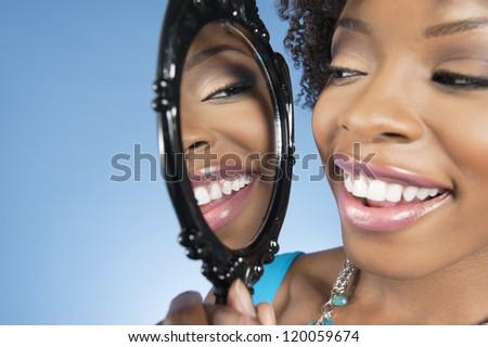 Close-up of a young woman looking at herself in mirror and smiling over colored background - stock photo