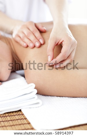 Close-up of a young woman receiving a acupuncture treatment in a spa center - stock photo