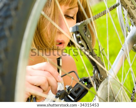 Close-up of a young woman repairing a bike - stock photo