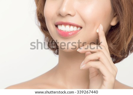 Close-up of a young woman's sensual mouth. A brunette beauty applying moisturizer on her skin. - stock photo