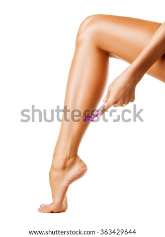Close-up of a young woman shaving legs isolated on white background - stock photo