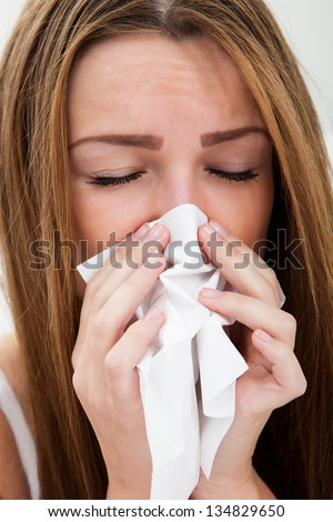 Close-up Of A Young Woman Sneezing In To Tissue - stock photo