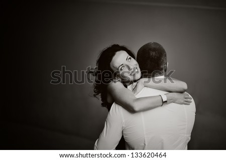 Close-up of a young woman tenderly embracing her boyfriend, black and white - stock photo